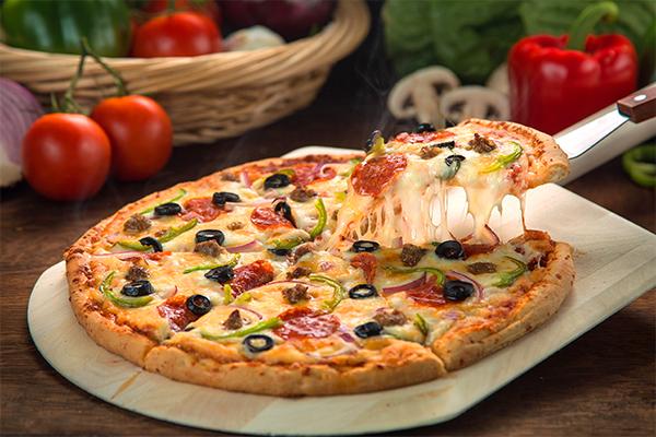 pizza caseira inteira, sendo retirada uma fatia