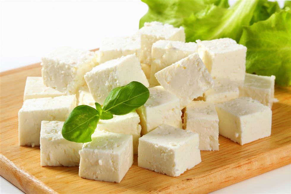 uma tábua com queijo branco cortado em cubos