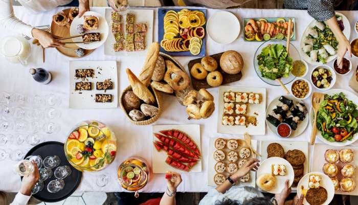 Mesa posta para um brunch, onde se encontram vários pratos e bebidas diferentes